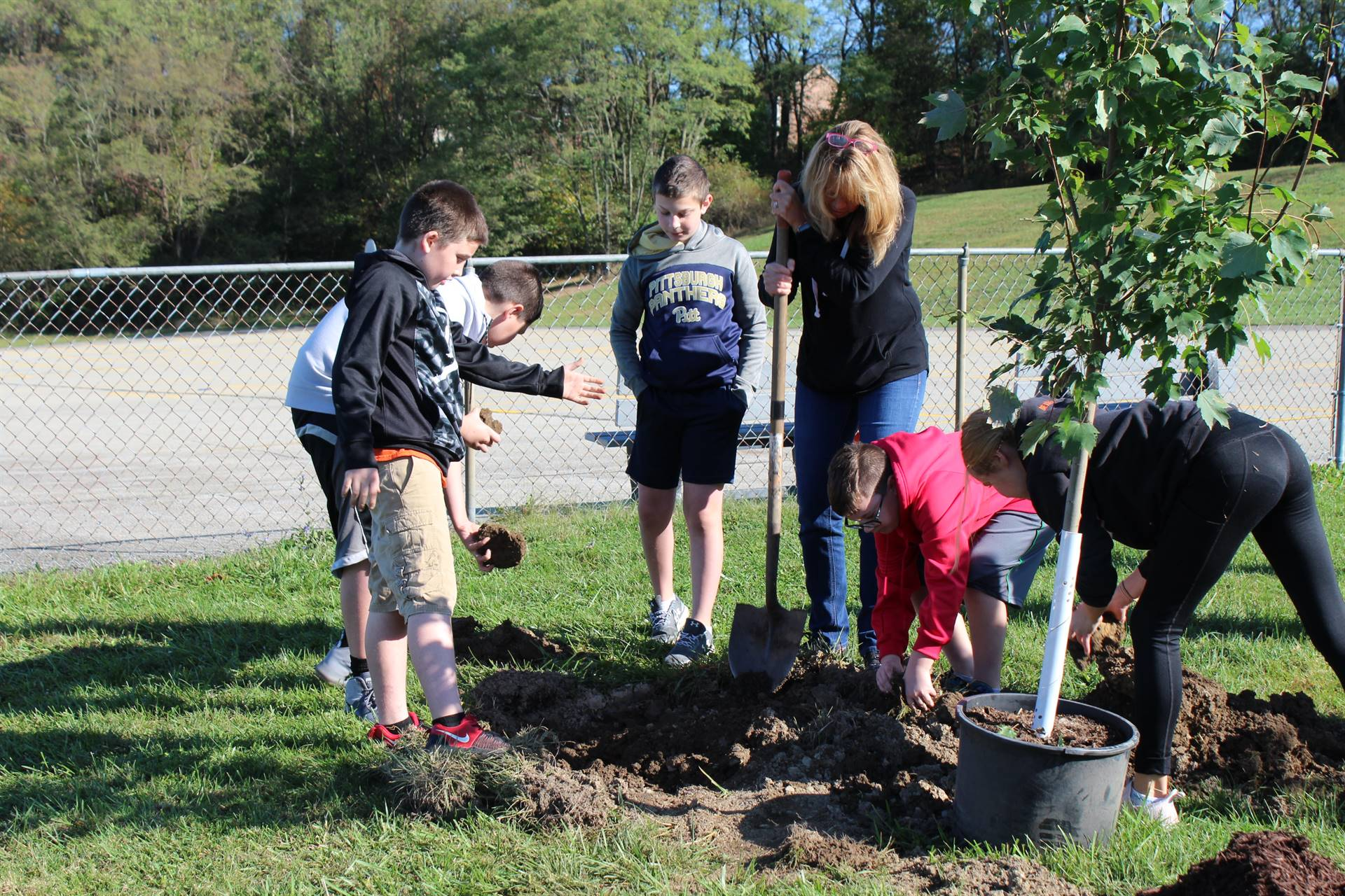 Four students and Mrs. Huwe planting a tree