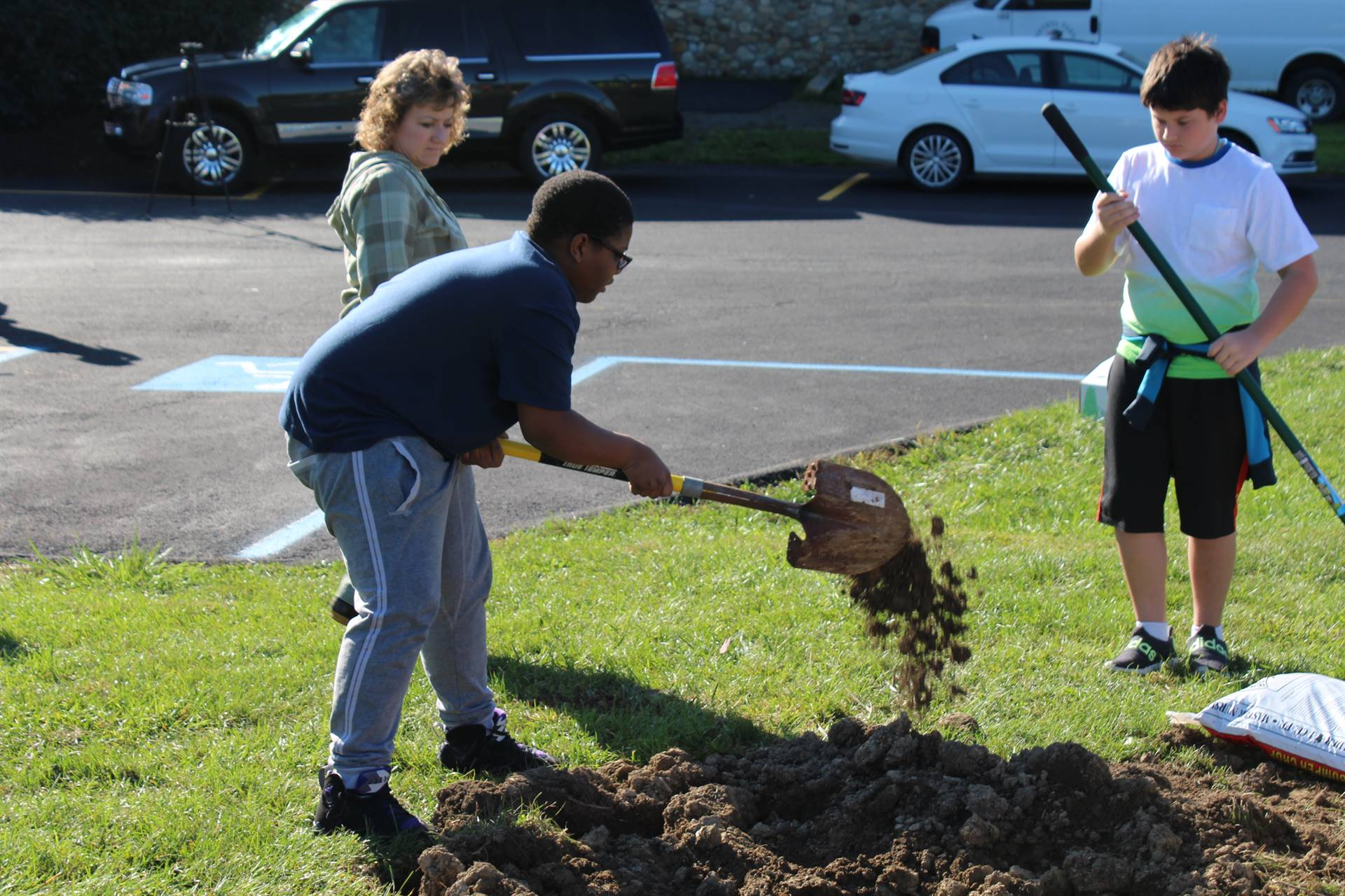 Student tossing dirt aside with a shovel