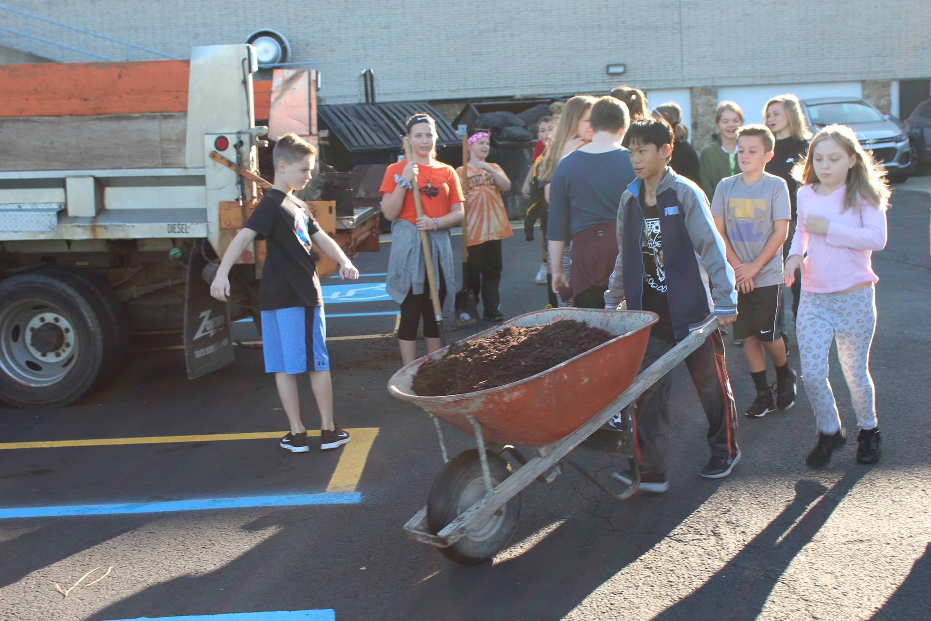 Student moving mulch with a wheelbarrow