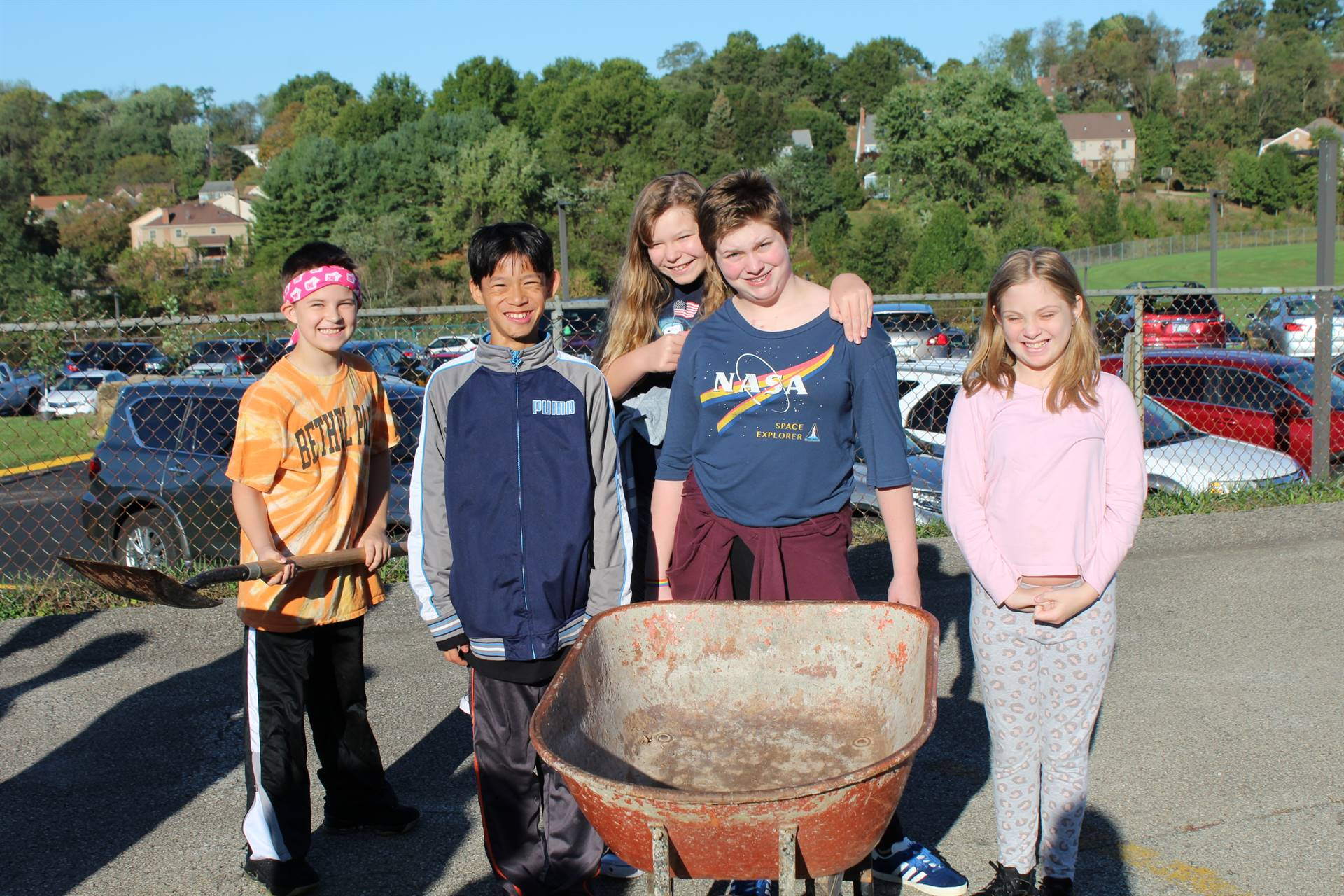 Students gathered around an empty wheelbarrow