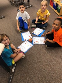 Four students writing about apples