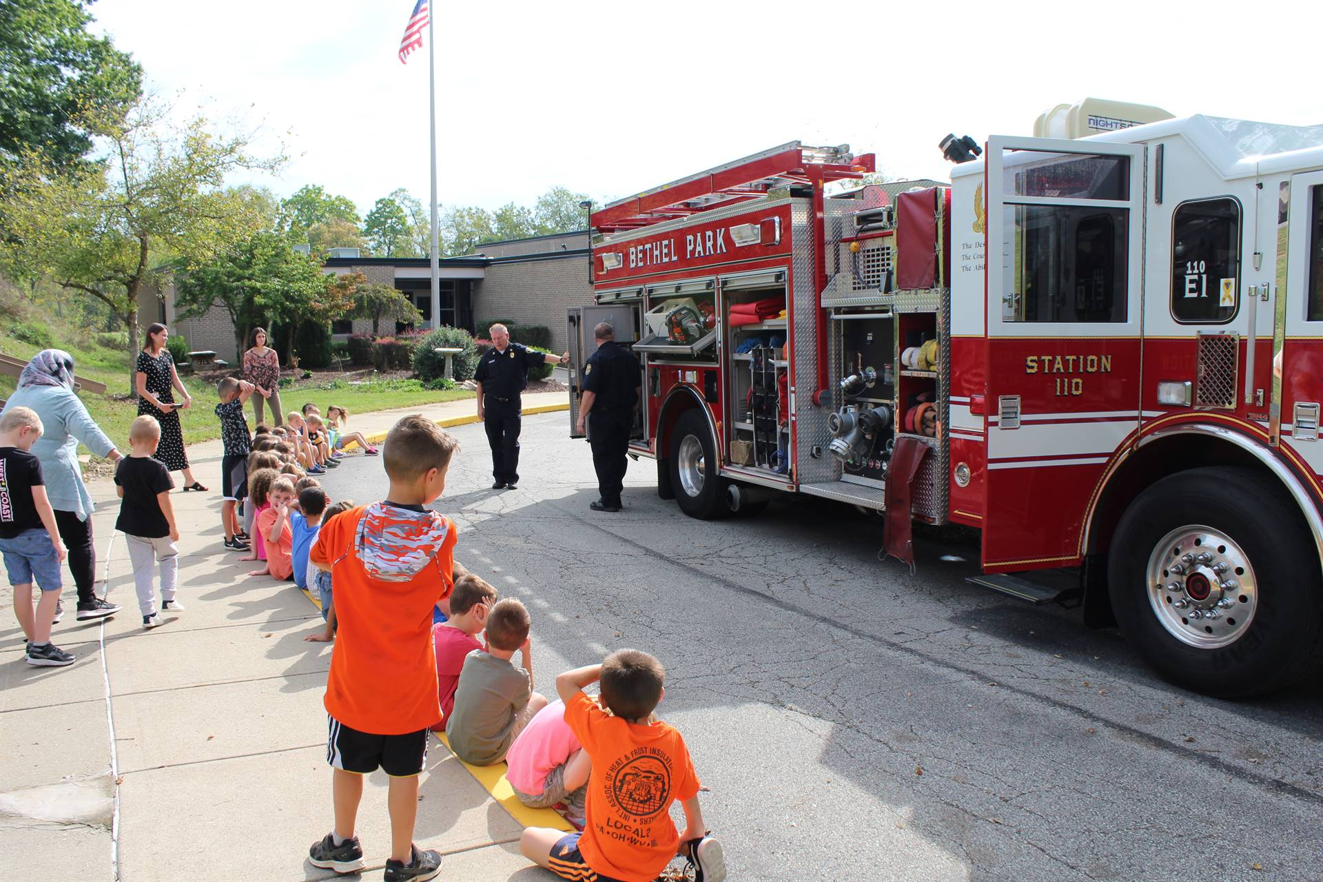 Students watching the firemen in front of the fire truck