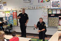 Two firemen talking to students