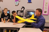 Mr. Muench holding a plane while two students look on