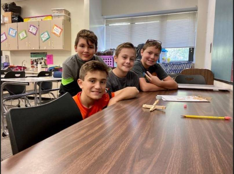 Four students with their catapult