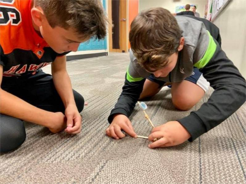Two students testing their catapult