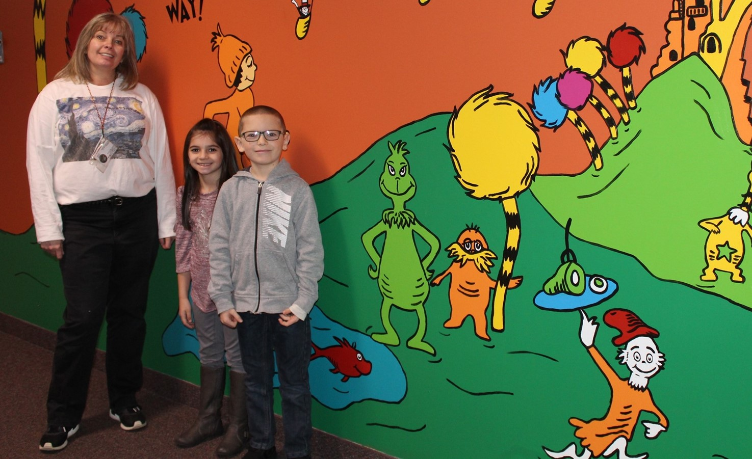 Teacher and two students in front of the Dr. Seuss wall