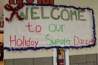Sign welcoming attendees to the Holiday Sweater Dance