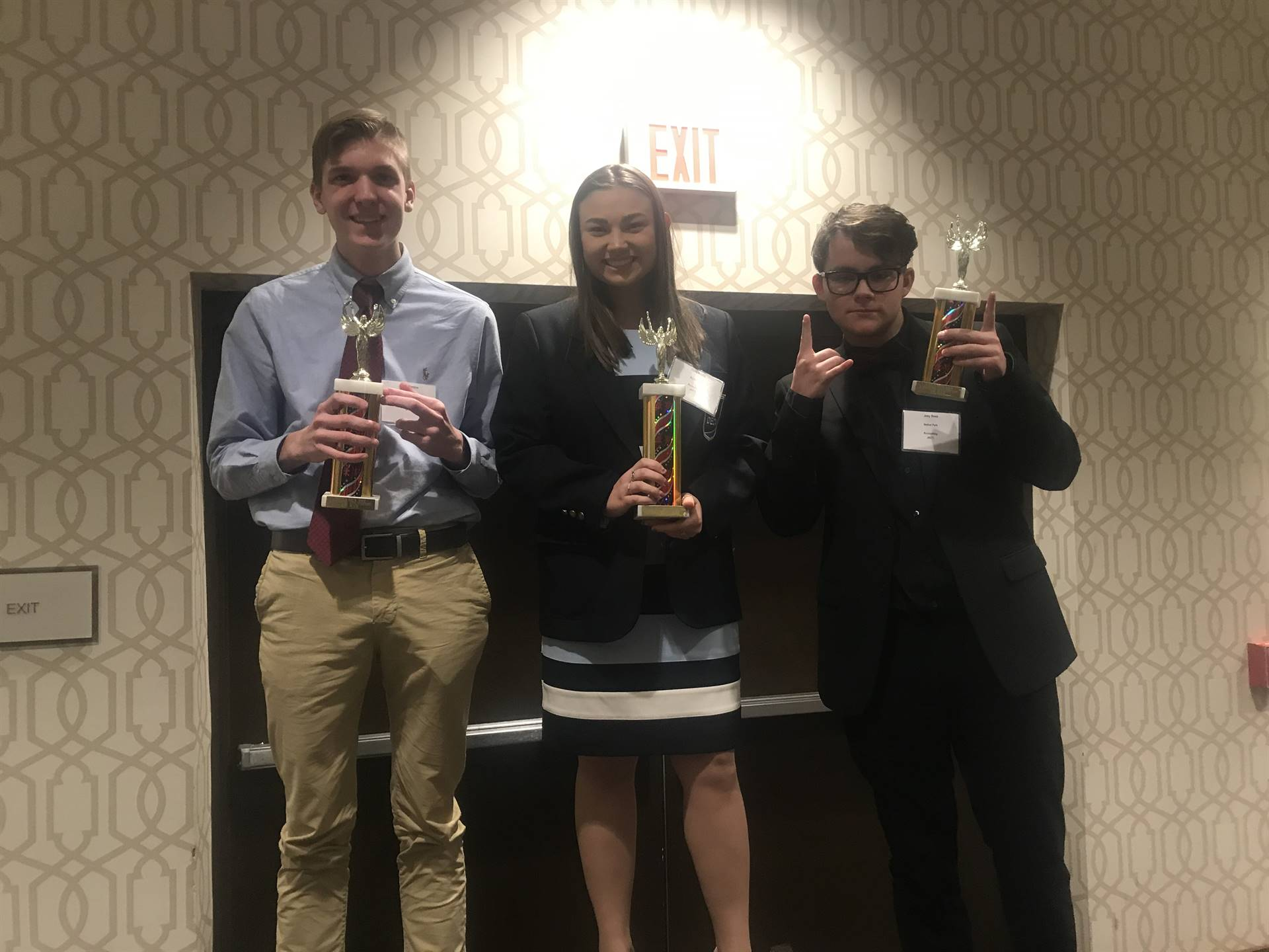 Three students holding their trophies
