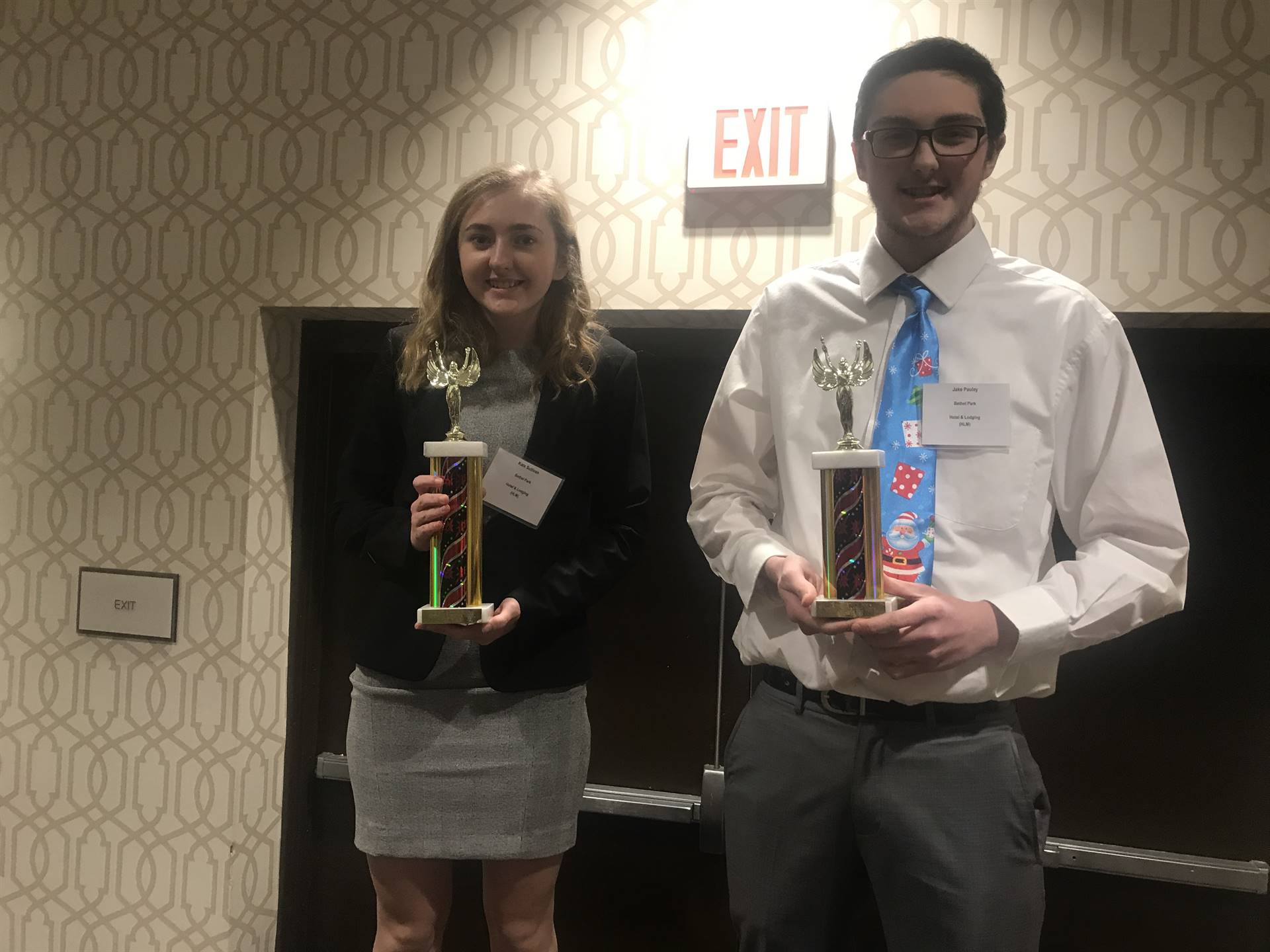 Two students holding their trophies