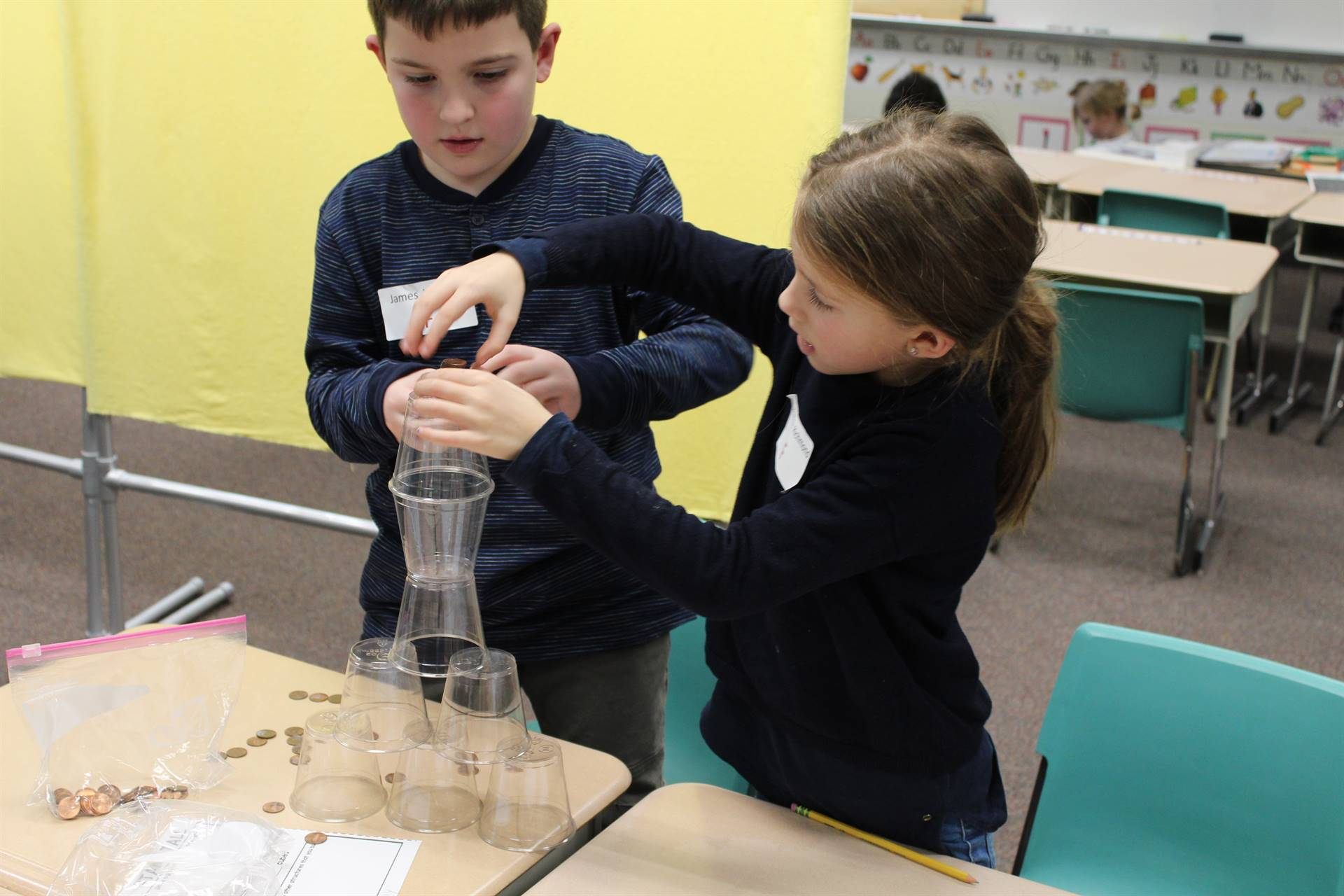 Two students building a tower out of plastic cups and pennies