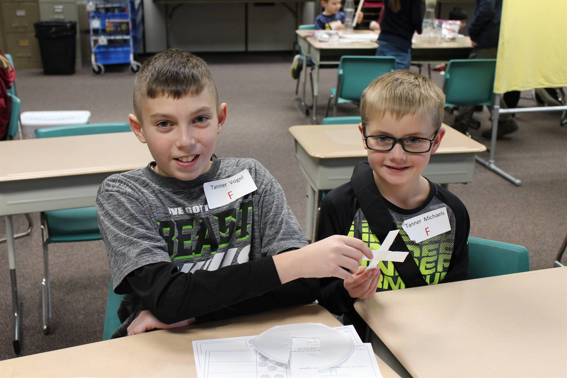 Two students building a spinning device