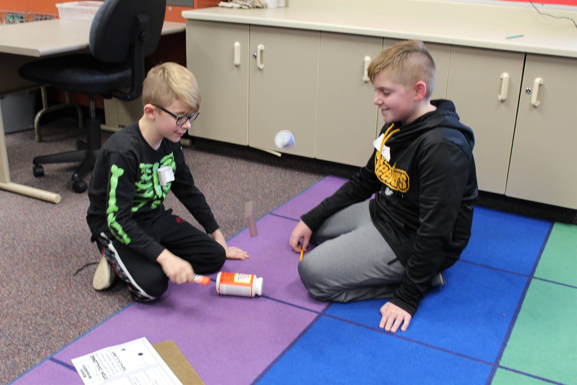 Two students launching something off a fulcrum