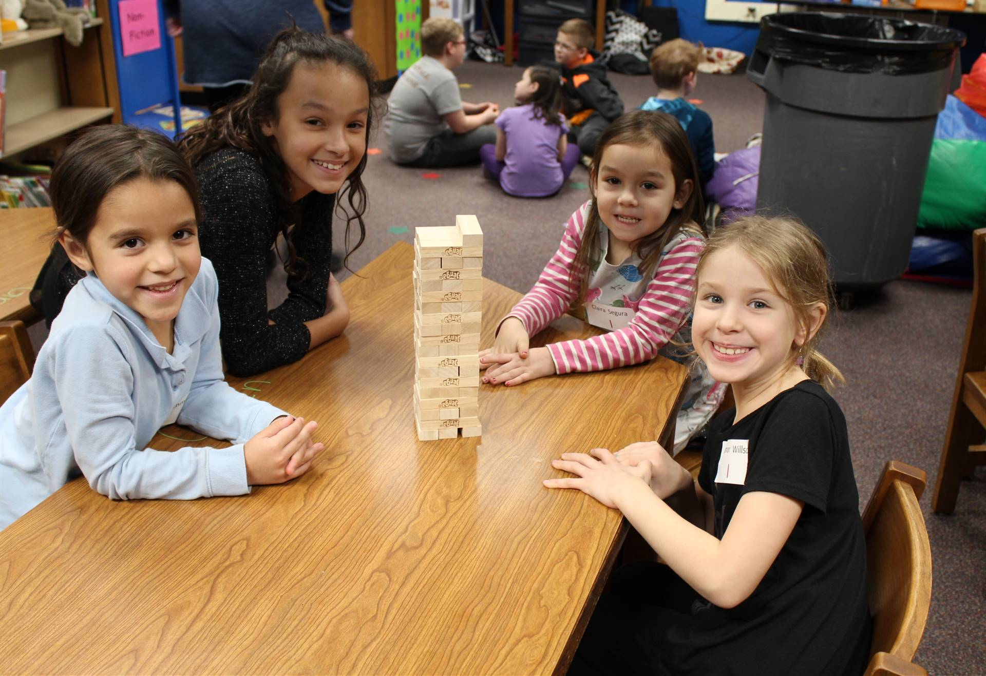 Four students playing Jenga