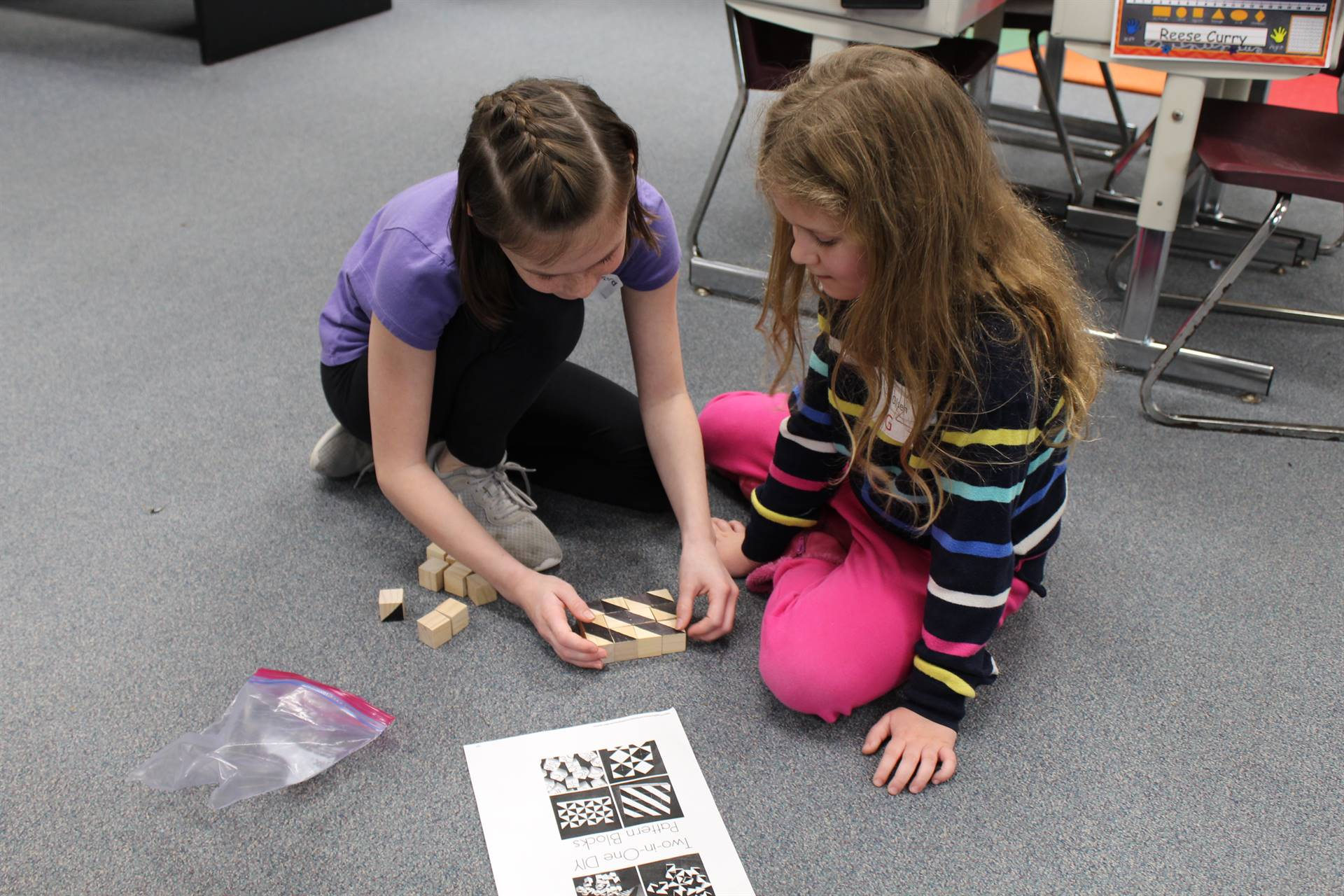 Two students arranging patterned blocks in a unique pattern