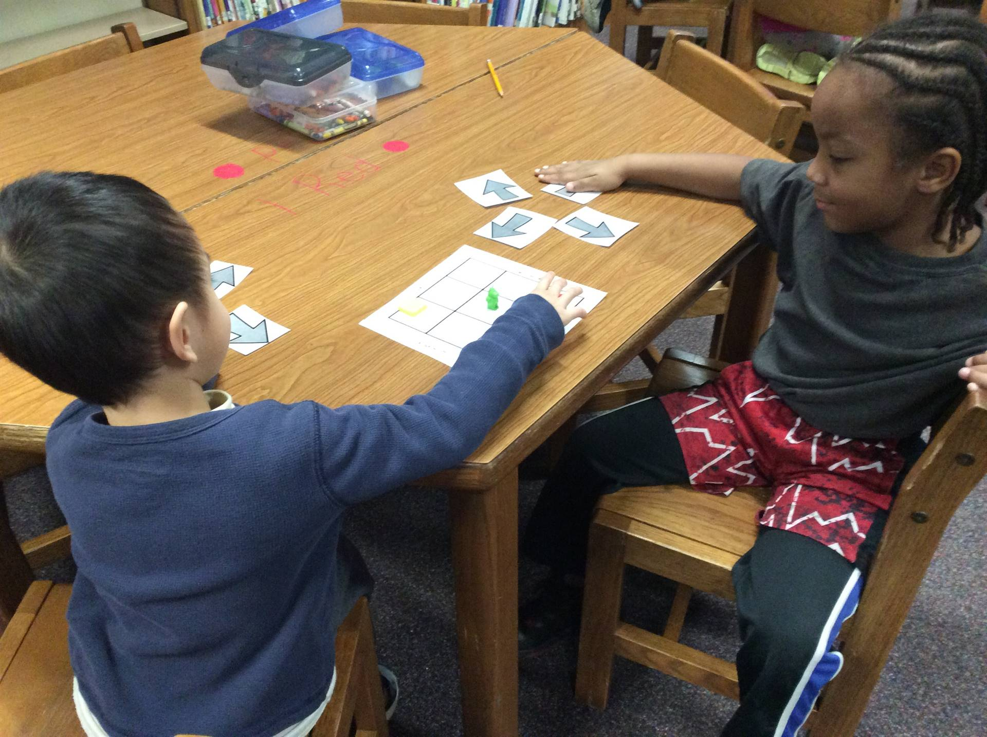 Two students playing a game at a table