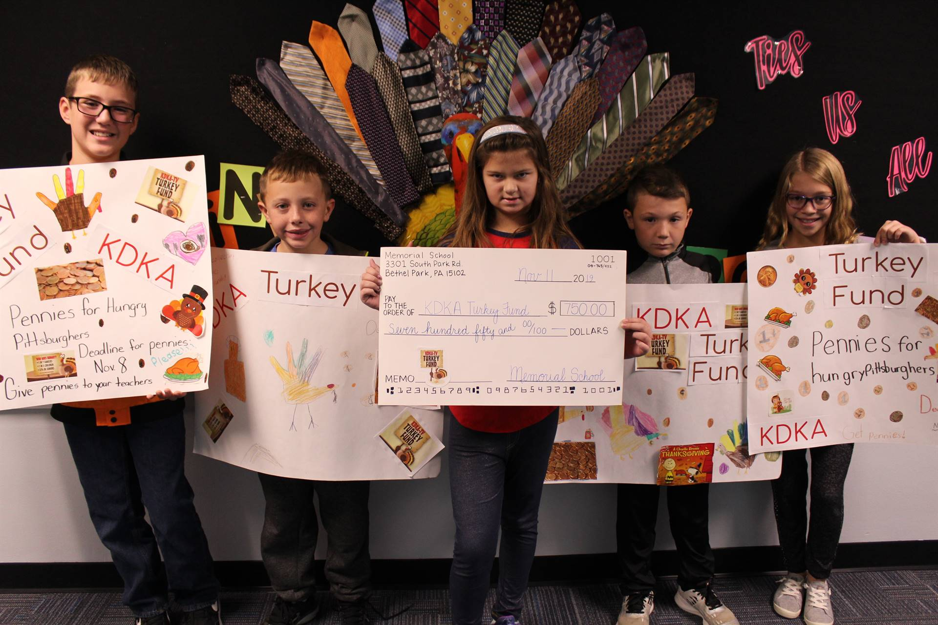 Five students holding the check and posters for the Turkey Fund