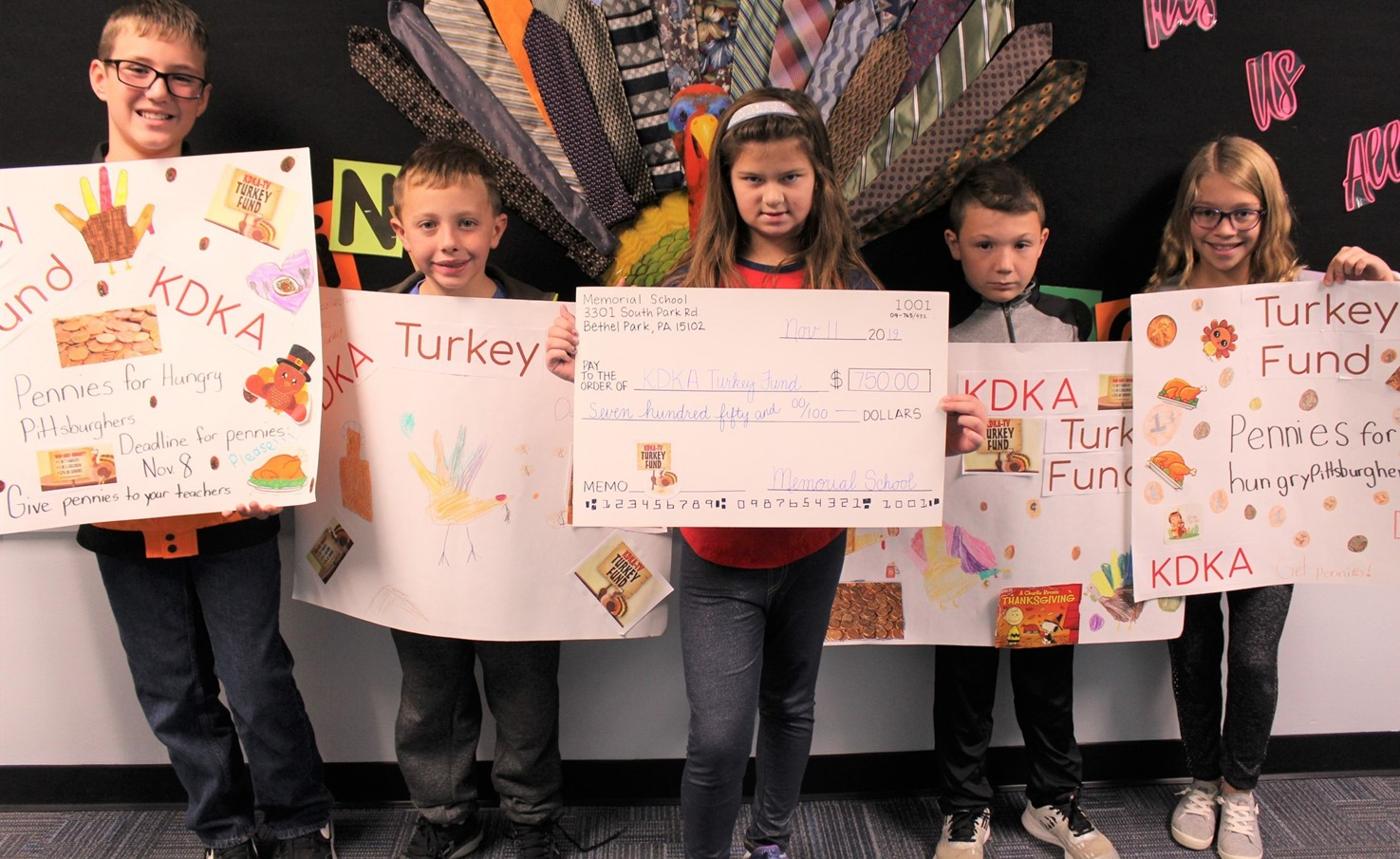 Five students holding a large check and posters