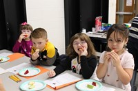 Four students tasting apples