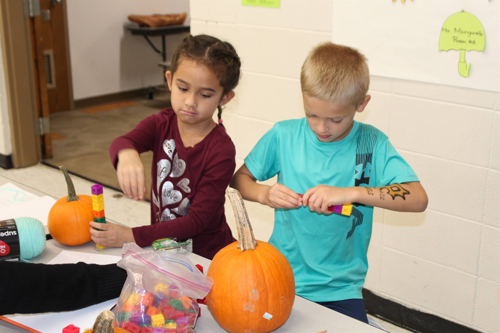 Two students measuring pumpkins