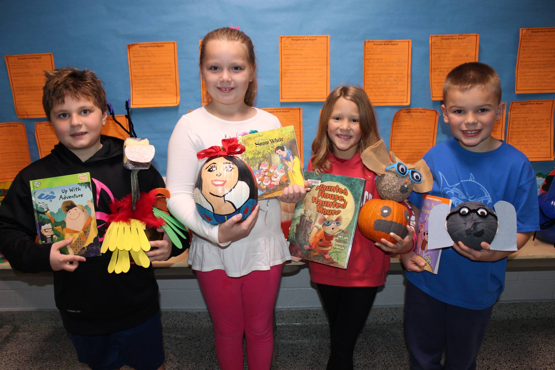 Four students holding their decorated pumpkins