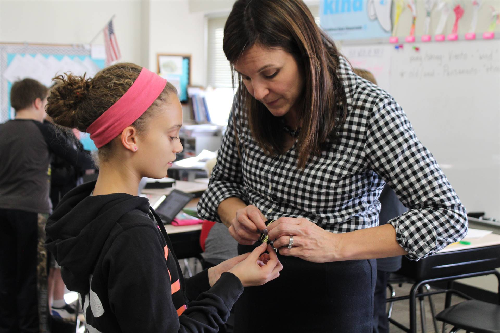 Mrs. Romito helping a student with her dream catcher