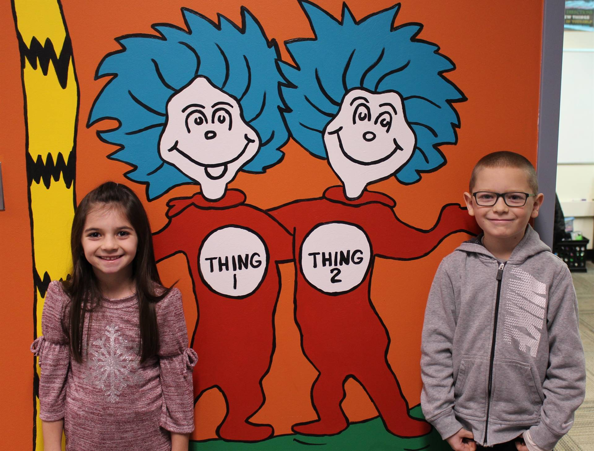 Two students in front of the Dr. Seuss wall