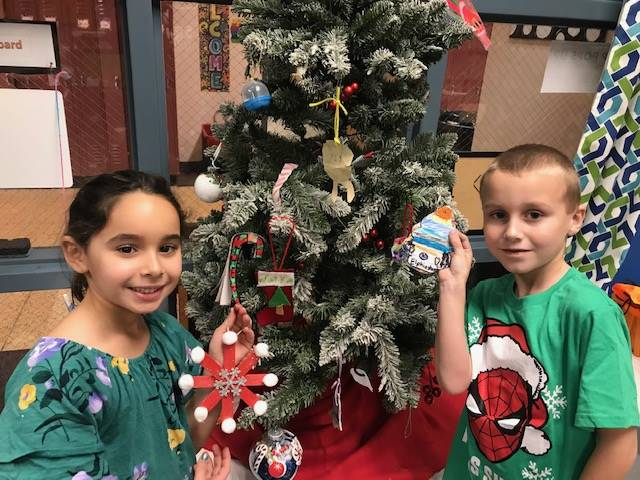Two students in front of the Maker Holiday Tree