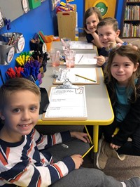 Four students writing about what they observed