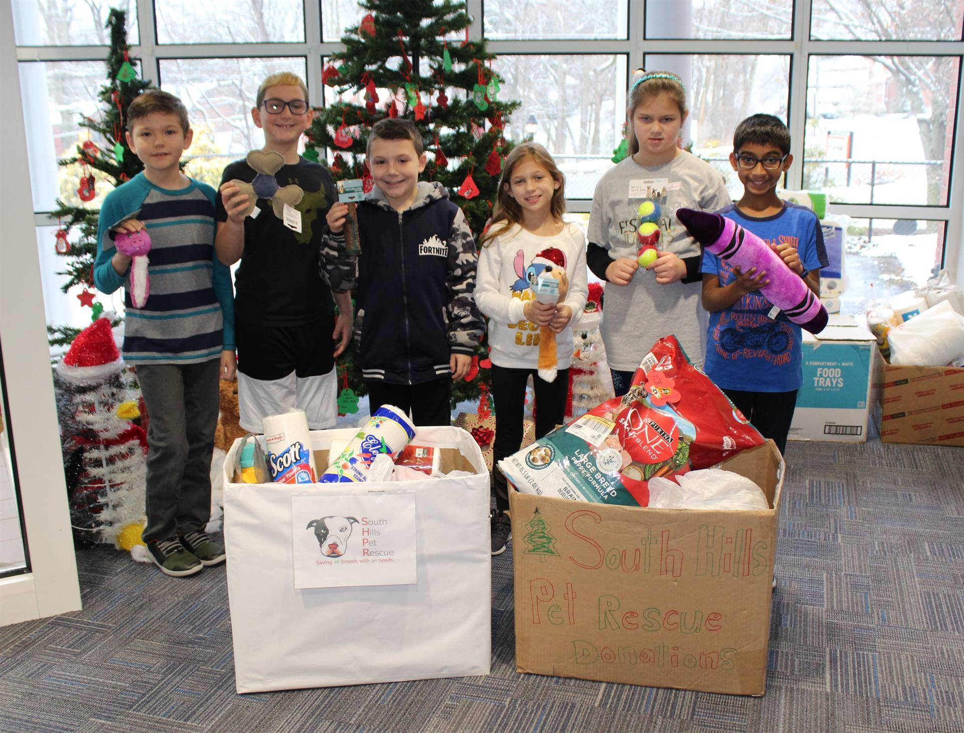 Six students with some of the pet drive supplies