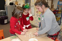 Three students building Santa's sled out of toothpicks and marshmallows