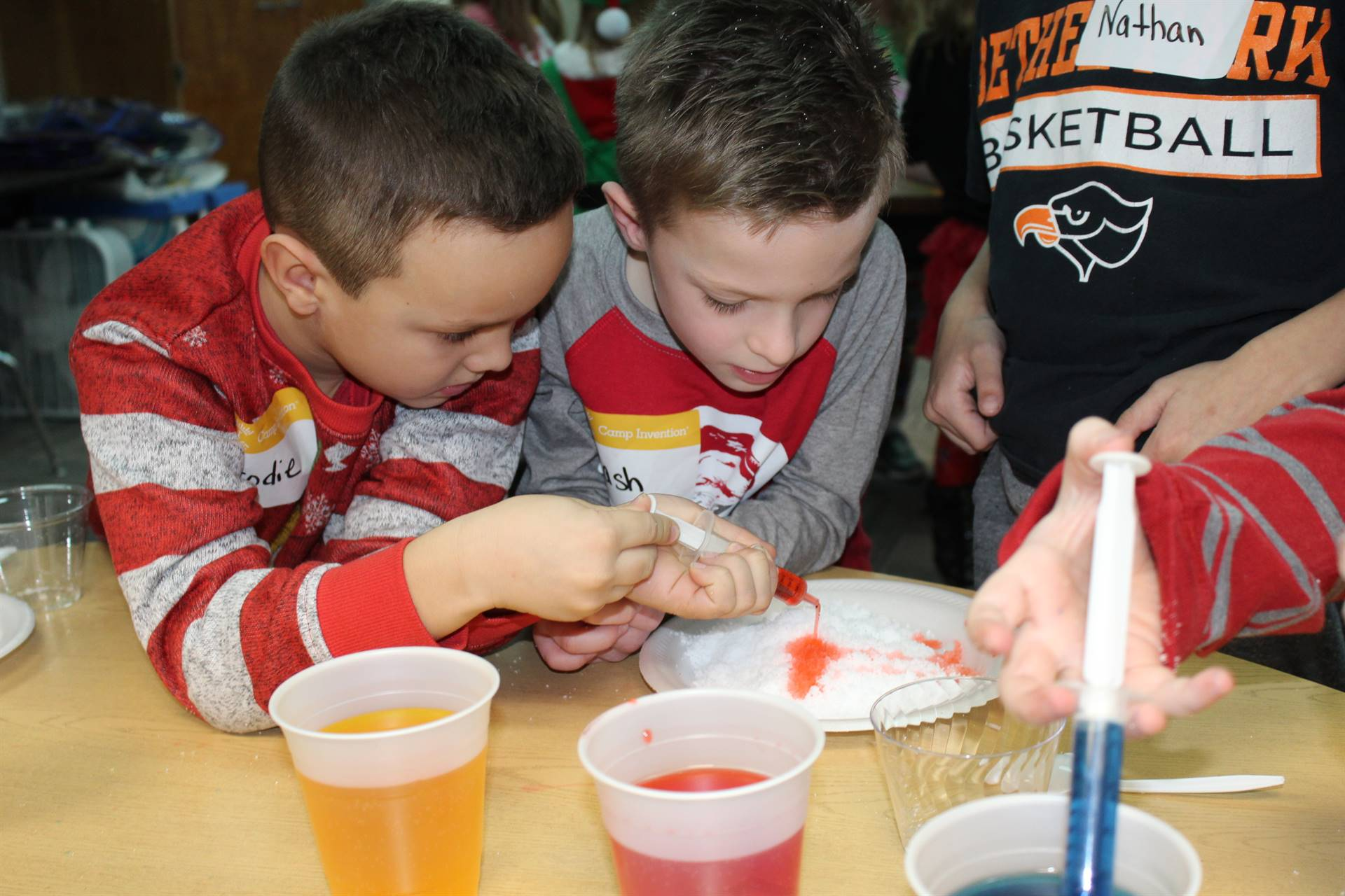 Two students adding orange food coloring to fake snow
