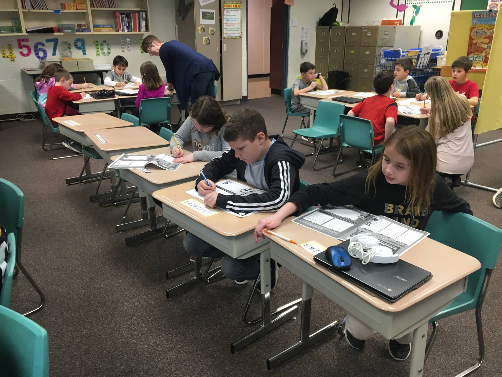 Three students working at desks during the Writers Club