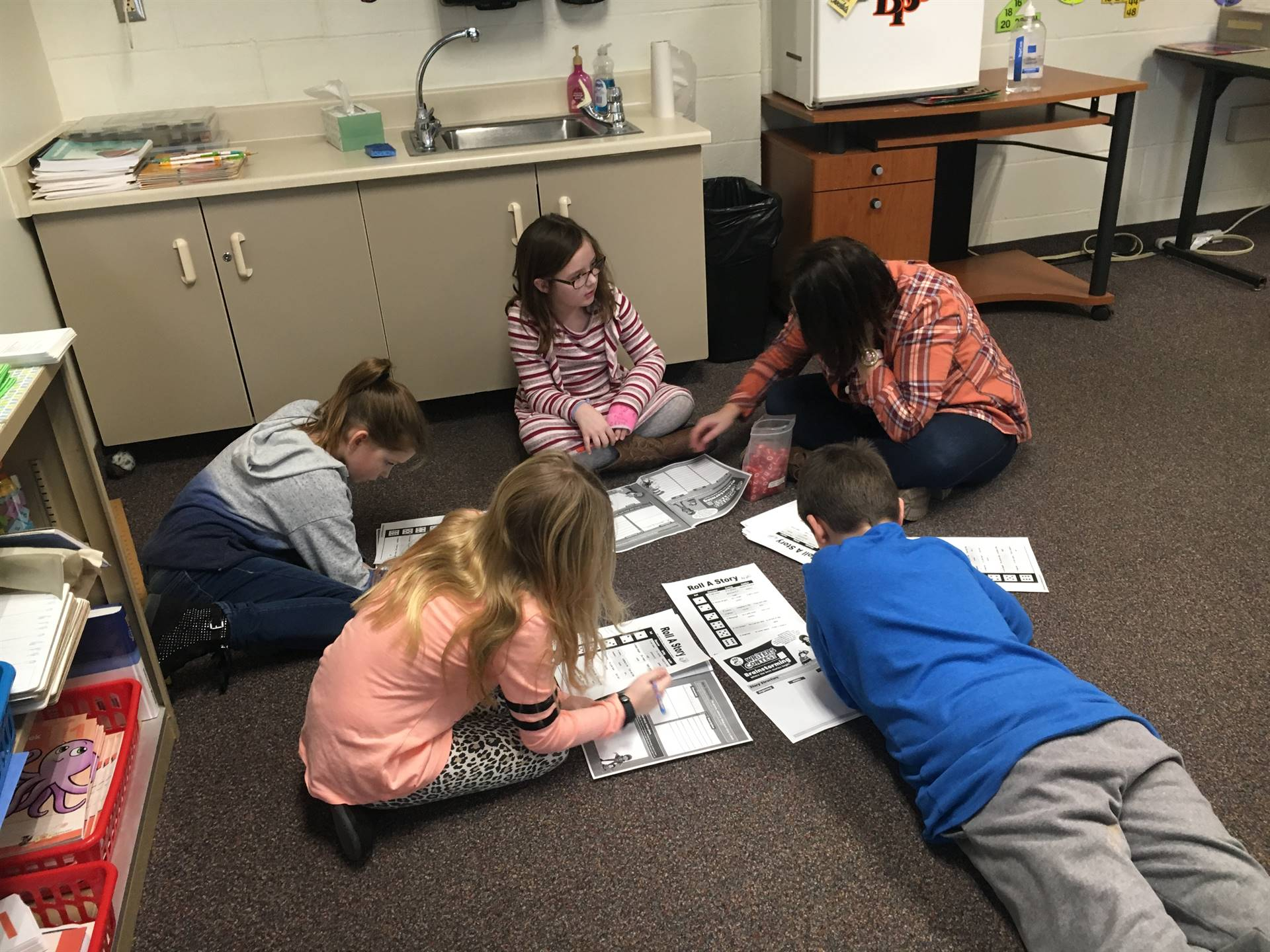 Five students working in a circle on the floor
