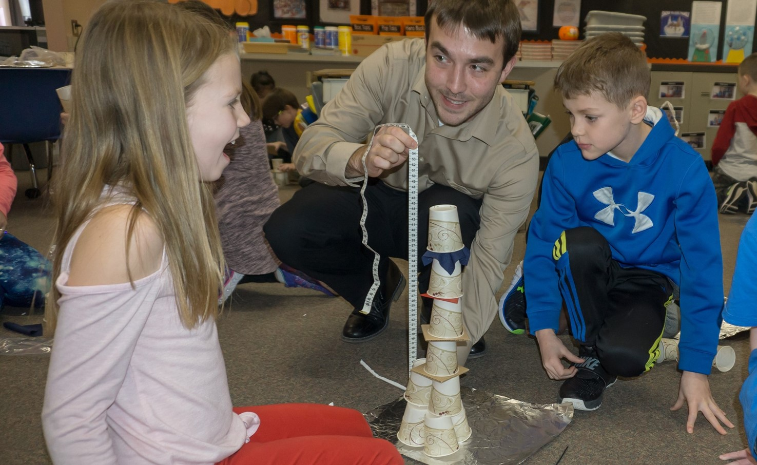 Two students look as teacher measures the height of their STEAM Tower