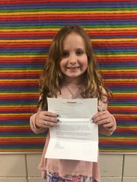 Ava with her letter telling her she is a winner