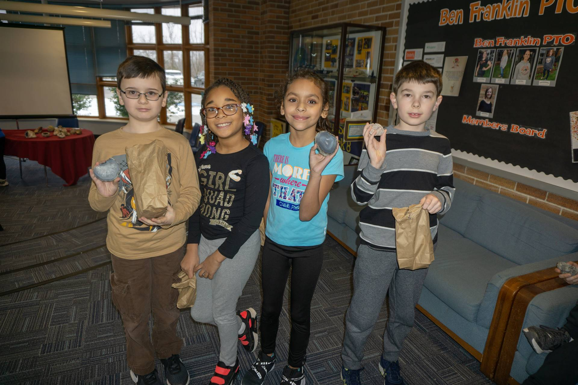 Four students holding geodes