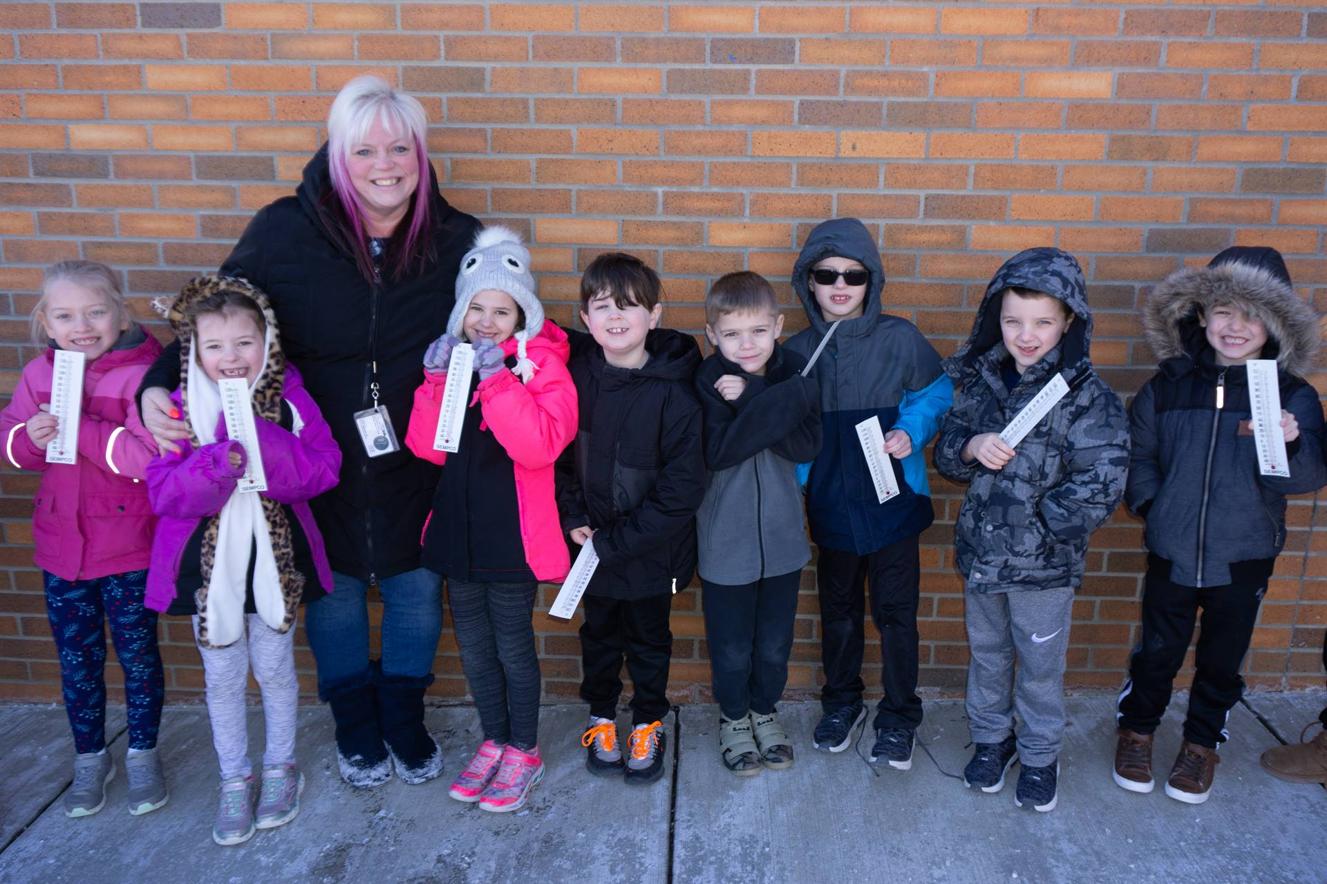 Mrs. Clancy and eight of her students holding thermometers