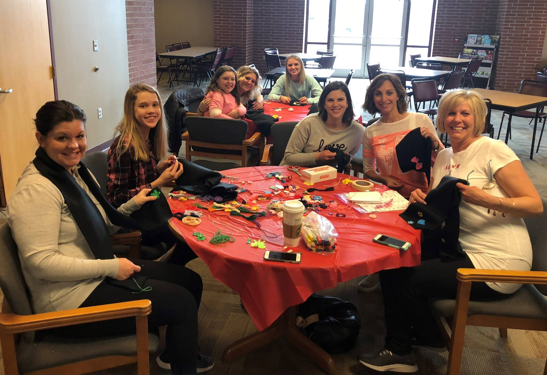 Eight Lincoln staff members making scarves