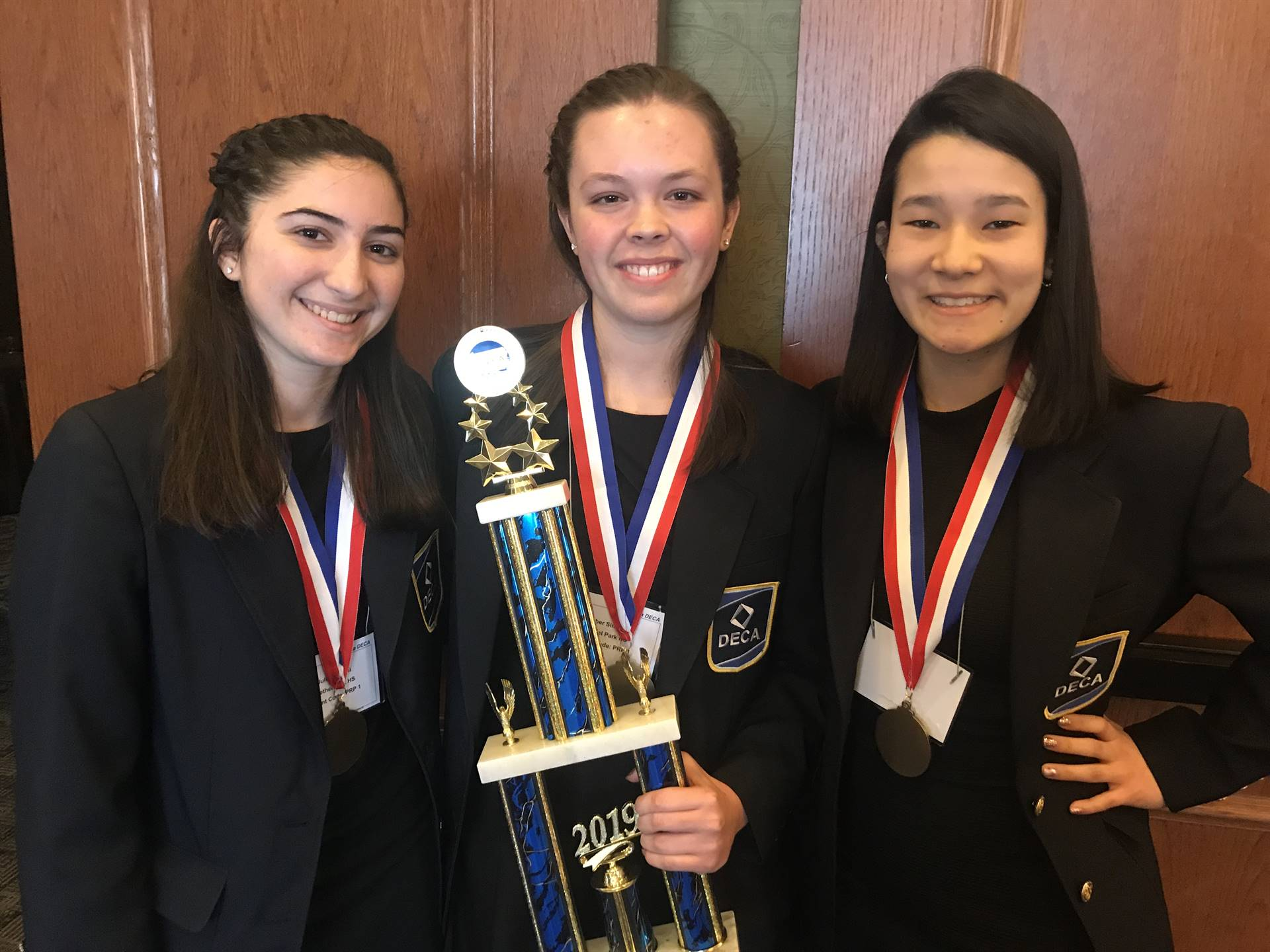 Three students with medals and trophy