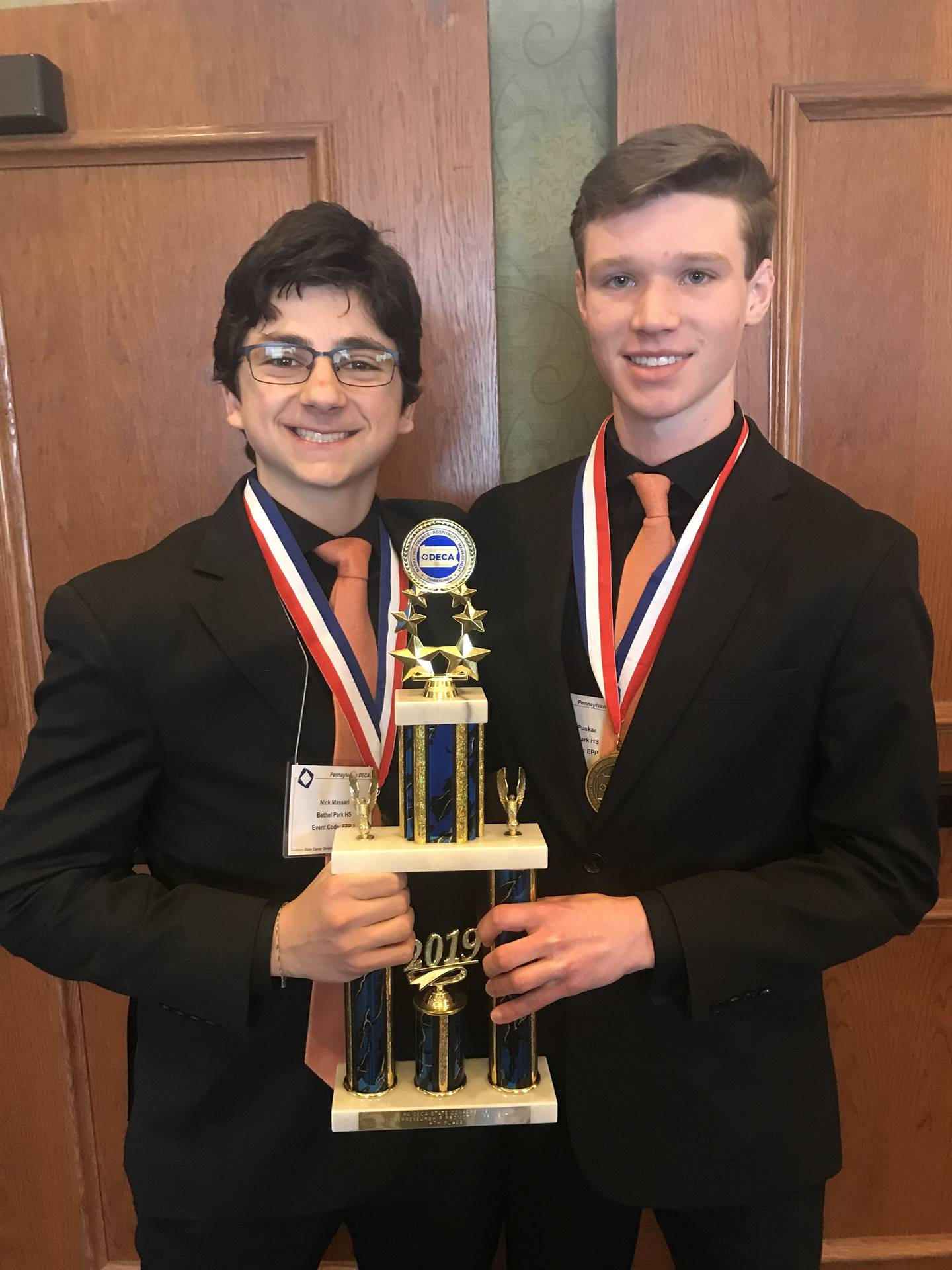 Two students with medals and trophy