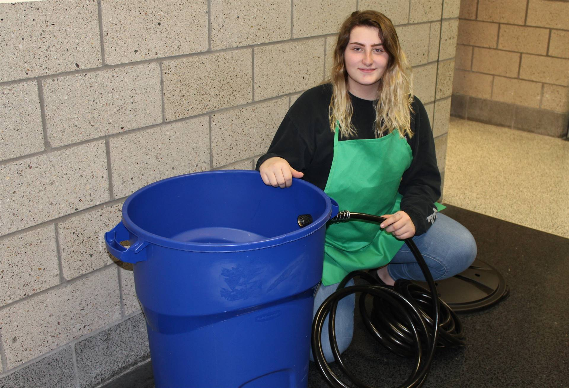 Student with a rain barrel she made out of an old trash can