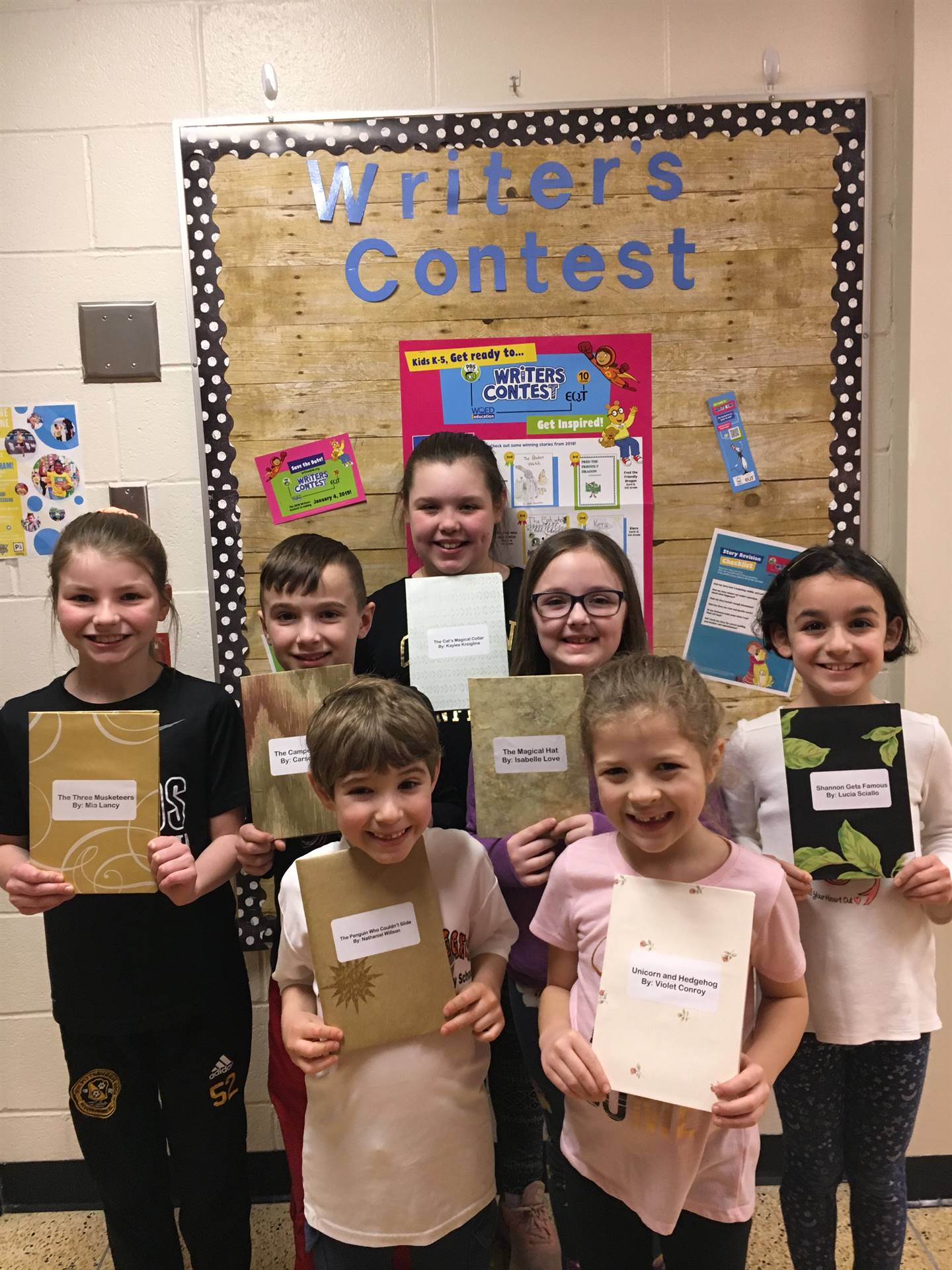 Seven students holding their original stories