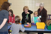 Mrs. Strotz shows families how to make a butterfly feeder