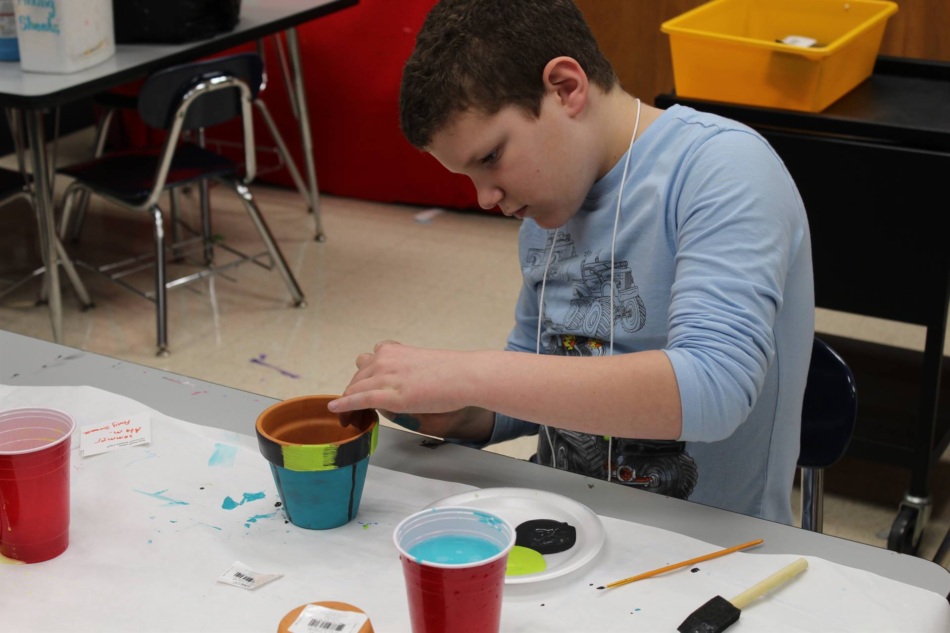 Student painting a terra cotta pot