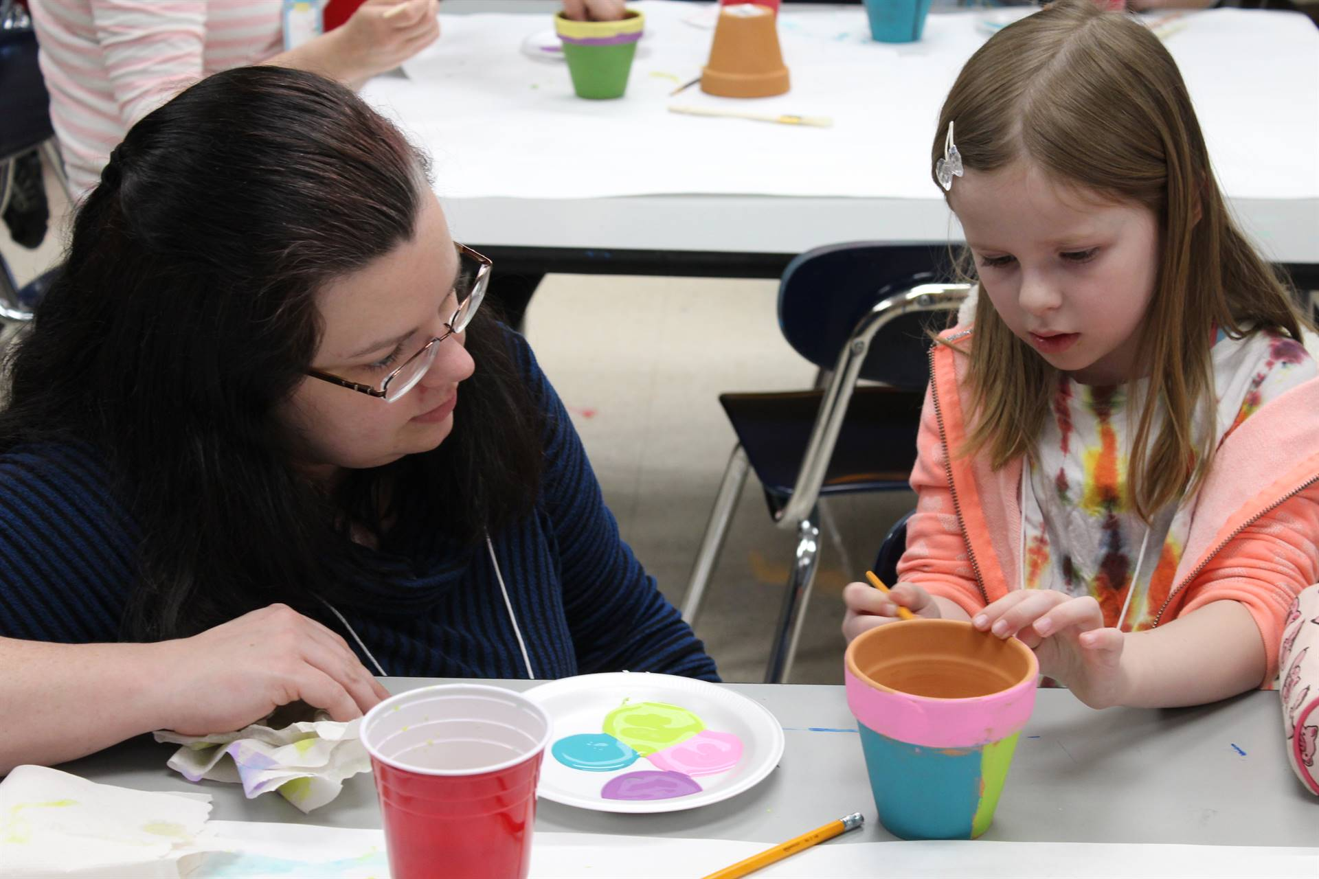 Student painting a terra cotta pot as her mother watches