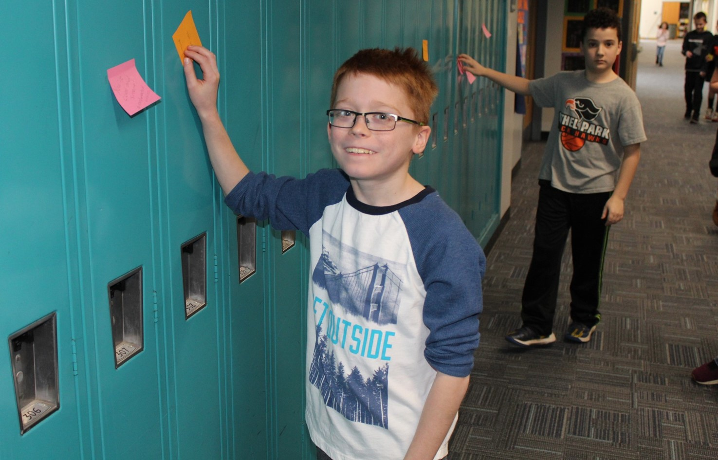 Two students putting sticky notes on lockers