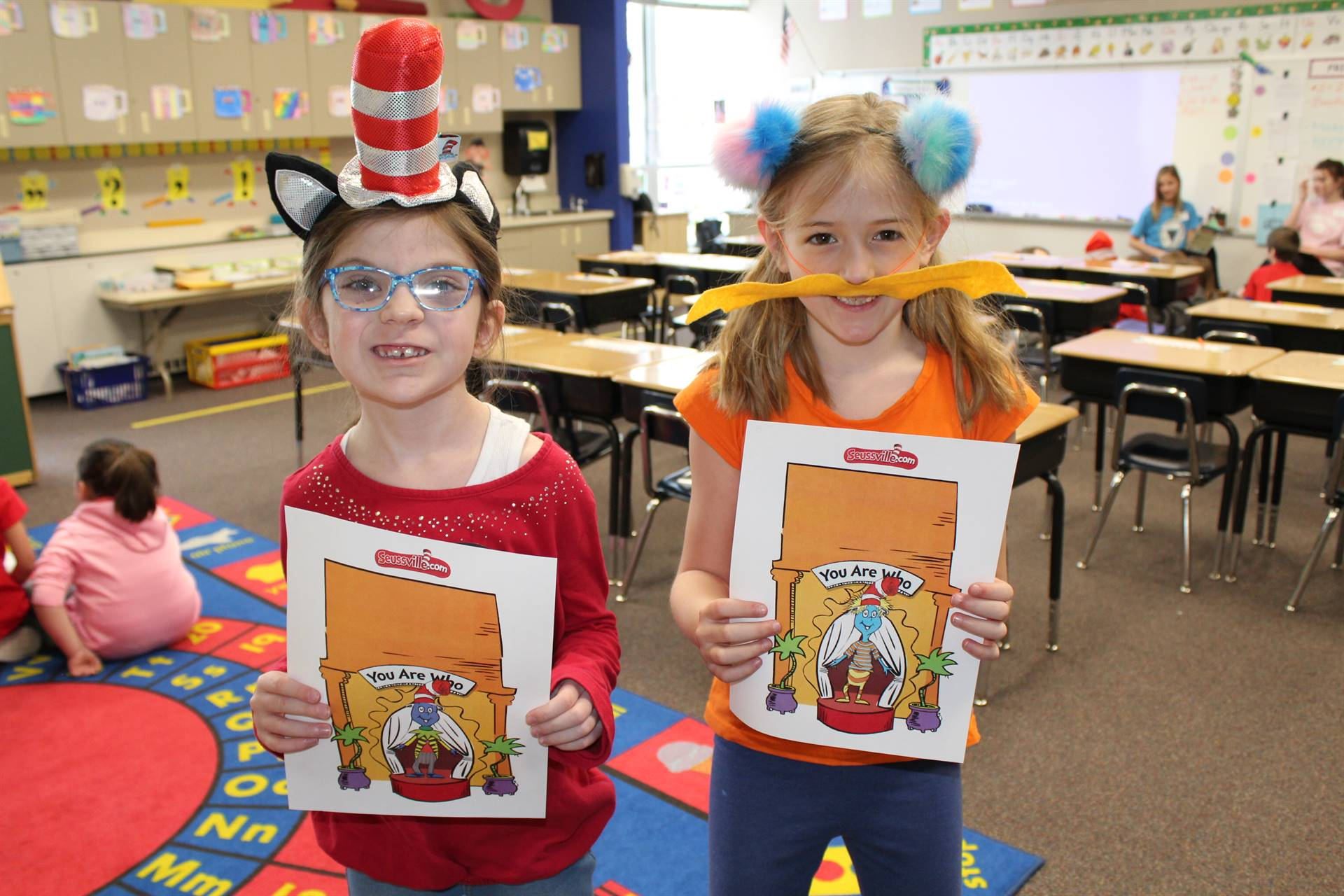 Two students holding their Dr. Seuss artwork