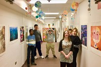 The students in the hallway with their mobiles above their heads
