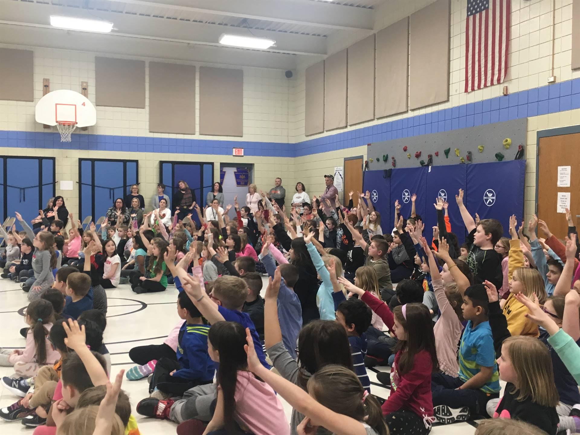 Students raising their hands at the kickoff assembly